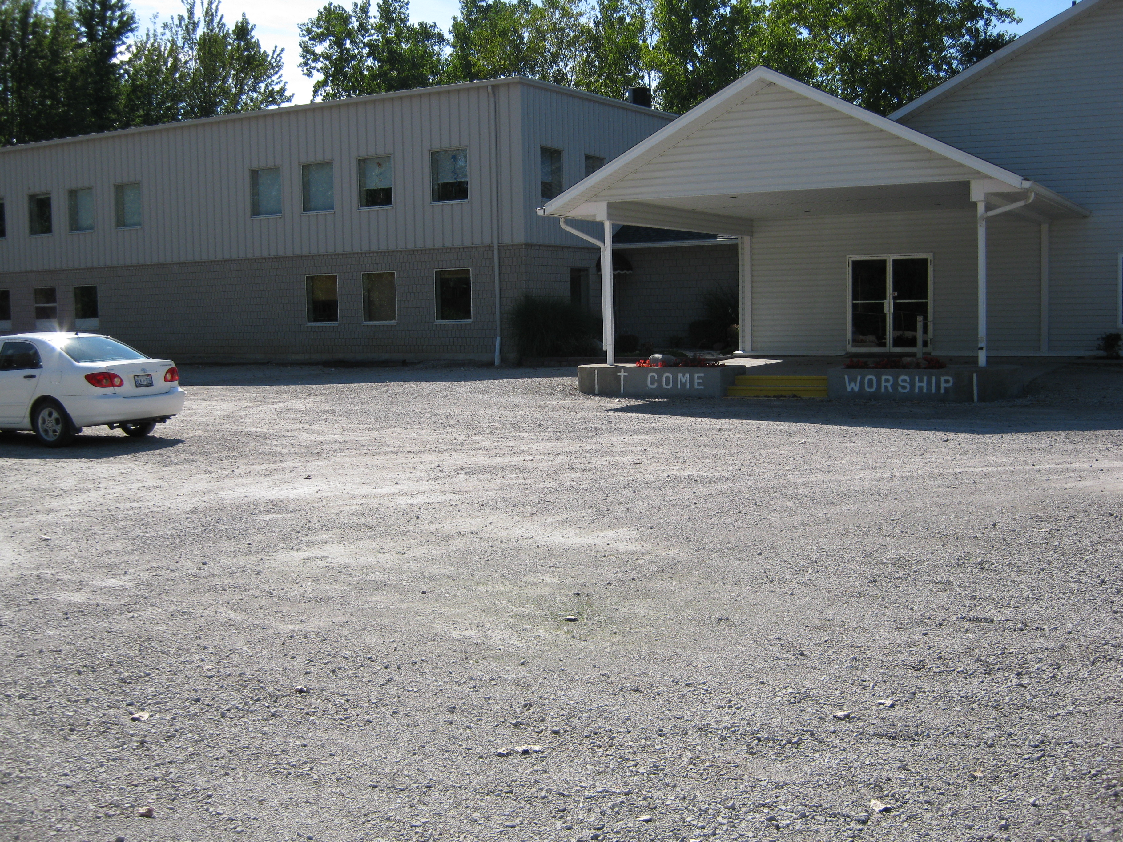 Car port at the entrance of the gray and white new building